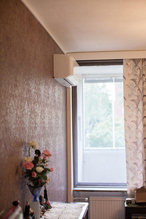 Ilmalämpöpumppu tapetoidulla seinällä ikkunan vieressä.